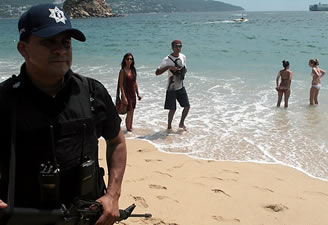 Tourists enjoy the beach near a police officer on patrol in Acapulco. The U.S. State Department issued a warning for Acapulco, its first for a popular tourist resort, after a year of violence in the city.